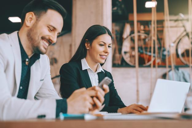 Zwei kollegen sitzen in der cafeteria und arbeiten am projekt. mann mit smartphone, während frau mit laptop. selektiver fokus auf frau. erst lernen, dann l. entfernen.