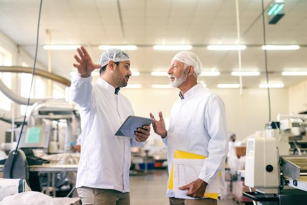 Zwei kollegen sprechen über arbeit, während sie in einer lebensmittelfabrik stehen. jüngeres hält tablett und älter hält diagramme.