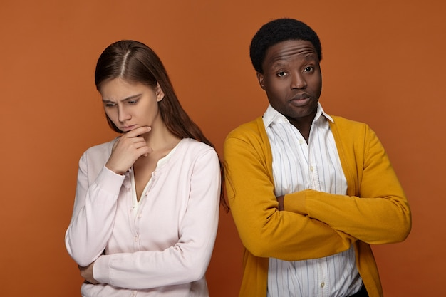 Zwei kollegen unterschiedlicher ethnien, die sich in geschäftlichen fragen nicht einig sind. afroamerikaner mit mürrischem blick verschränkt die arme auf der brust und spricht nicht mit besorgter nachdenklicher kaukasischer frau
