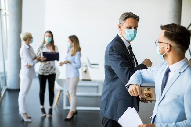 Zwei kollegen vermeiden einen handschlag, wenn sie sich im büro treffen, und grüßen mit stoßenden ellbogen