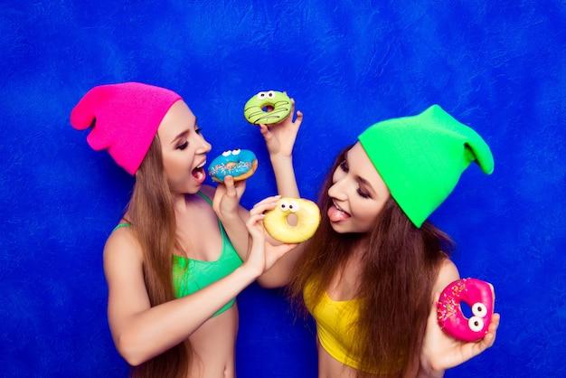 Zwei komische junge frauen, die einen köstlichen donut essen