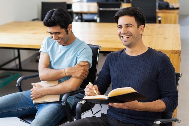 Zwei kommilitonen studieren, lesen lehrbücher und lachen