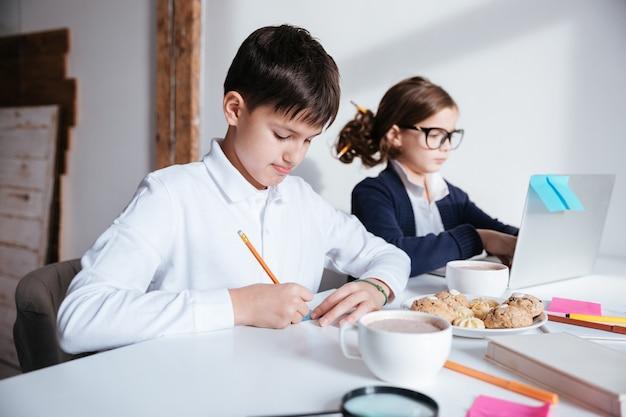 Zwei konzentrierte kleine kinder mit laptopschreiben und frühstücken am tisch