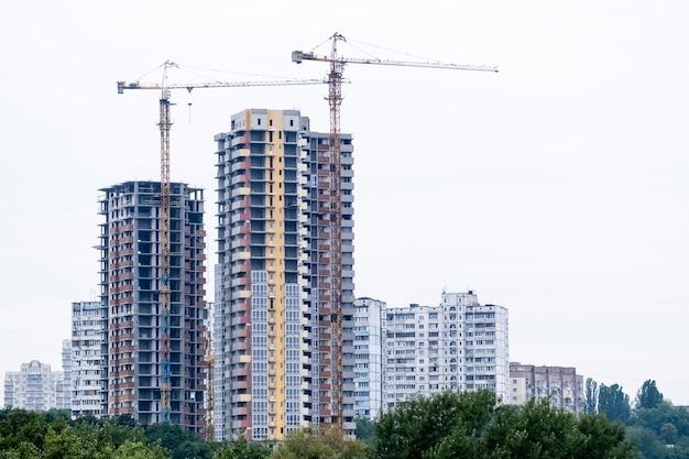 Zwei kräne auf einer baustelle des gebäudes eines modernen wohnviertels hohe wohngebäude oder wolkenkratzer in einem neuen elite-komplex.