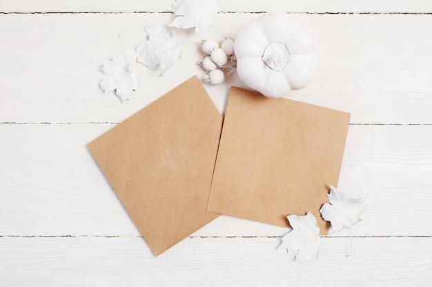 Zwei kraftpapierblätter, weißer kürbis, beeren und blätter