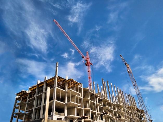 Zwei kraniche, die wohnhaus am hintergrund des blauen himmels des tageslichts bauen. baukonzept