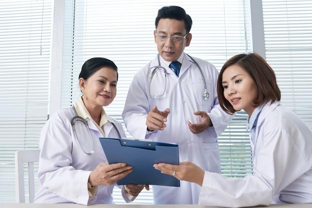 Zwei krankenschwestern, die dem chefarzt bericht erstatten