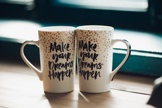 Zwei kreative dekotassen mit warmem tee oder kaffee.