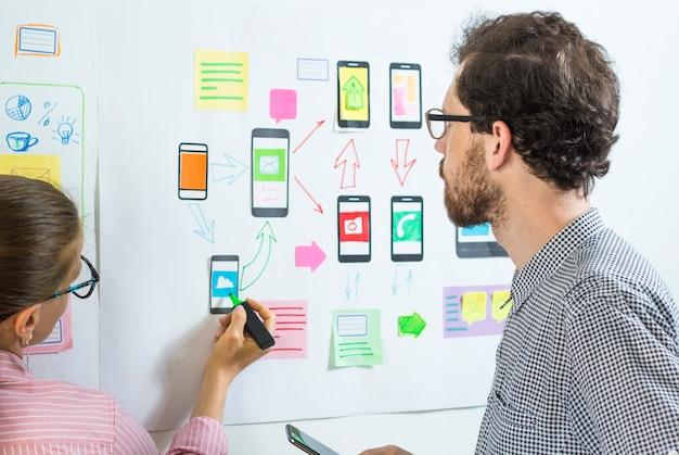 Zwei kreative designer entwickeln mobile anwendungen am arbeitsplatz.