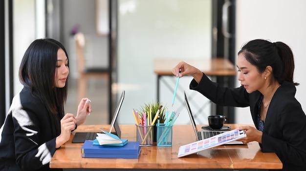 Zwei kreative geschäftsfrauen diskutieren und strategie des geschäftserfolgs im modernen büro.