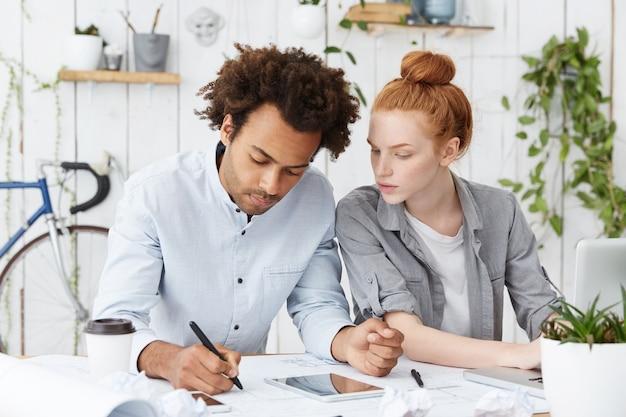 Zwei kreative kollegen, die am schreibtisch zusammenarbeiten