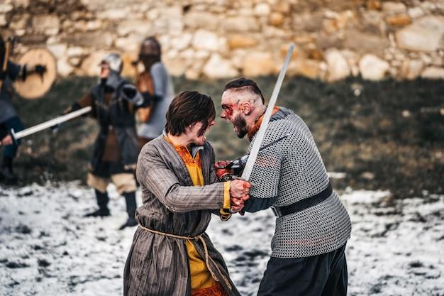 Zwei krieger in rüstung mit waffen, die mit schwertern kämpfen. nahaufnahme von emotionen auf dem gesicht eines mit blut verschmierten kriegers