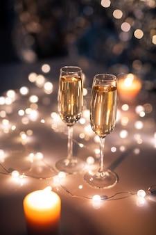 Zwei kristallflöten mit funkelndem champagner auf dem tisch, umgeben von brennenden girlanden und brennenden kerzen in festlicher umgebung
