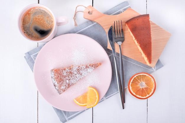 Zwei kuchenstücke auf einem rosa teller und ein schneidebrett mit messer und gabel auf einer gefalteten leinenserviette und eine tasse mit kaffee