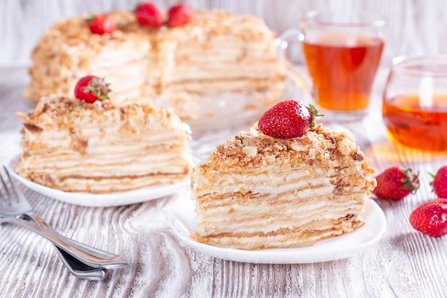 Zwei kuchenstücke napoleon auf weißem teller. russische küche, mehrschichtiger kuchen mit gebäckcreme, nahaufnahme