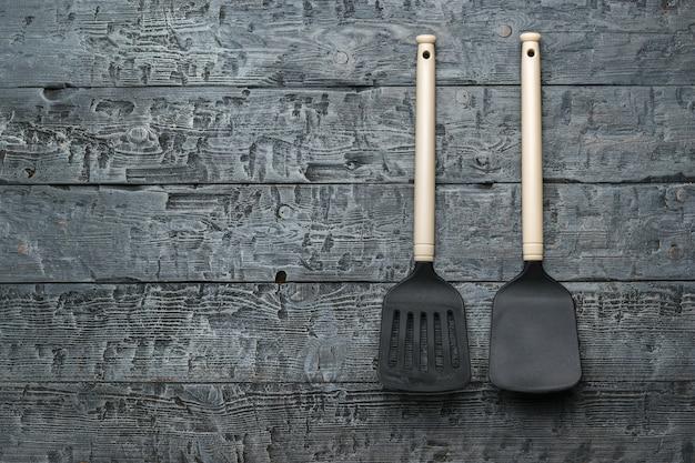 Zwei küchenspatel mit beigefarbenen griffen auf holzhintergrund. küchengeräte.