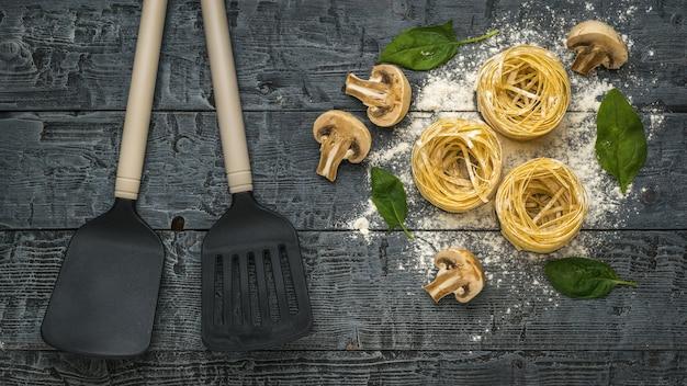 Zwei küchenspatel, nudeln und pilze auf einer holzoberfläche. zutaten für die herstellung von nudeln.