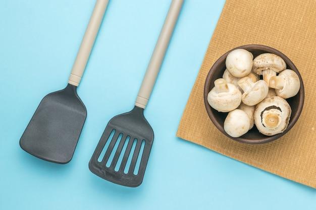 Zwei küchenspatel und eine tonschüssel mit pilzen auf blauem grund. eine beliebte pilzsorte.