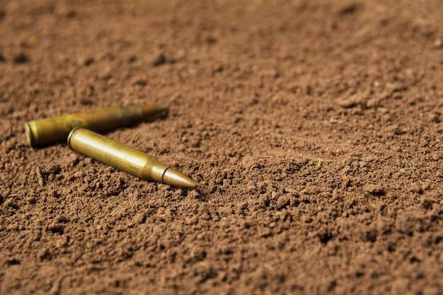 Zwei kugeln, maschinengewehrkugeln auf bodenhintergrund
