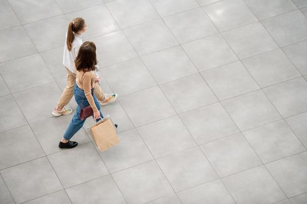 Zwei kundinnen in freizeitkleidung gehen das große zeitgenössische handelszentrum entlang, während sie am schwarzen freitag einkaufen