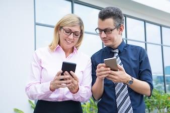 Zwei lächelnde Geschäftskollegen, die draußen Telefone verwenden.