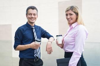 Zwei lächelnde Geschäftspartner, die Mitnehmerkaffee trinken.