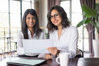 Zwei lächelnde weibliche Mitarbeiter, die Dokument im Café besprechen.