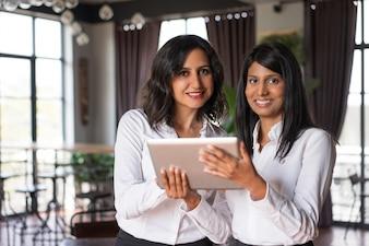 Zwei lächelnde weibliche Mitarbeiter, die Tablet-Computer im Café verwenden.