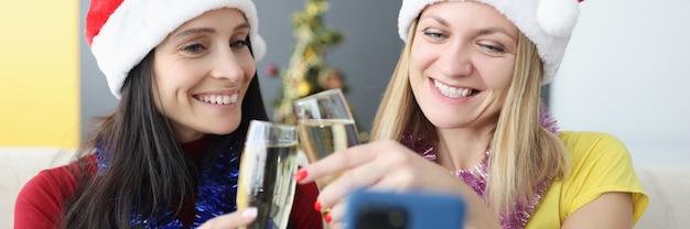 Zwei lachende frauen in weihnachtsmannhüten schauen auf den smartphonebildschirm und halten gläser champagner