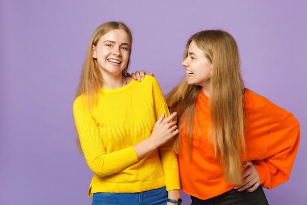 Zwei lachende junge blonde zwillingsschwestern mädchen in lebendigen bunten kleidern stehen und sehen sich einzeln auf pastellvioletter blauer wand an. menschen-familien-lifestyle-konzept.