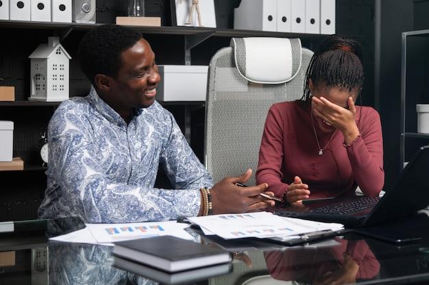 Zwei lachende junge schwarze haben spaß daran, ihr geschäft zu besprechen, das am schreibtisch im büro sitzt