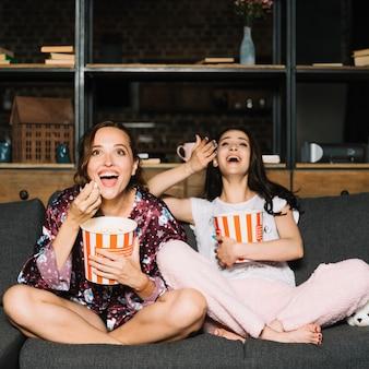 Zwei lachende weibliche freunde beim aufpassen des komödienfilms