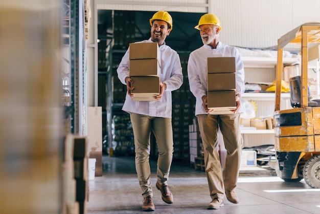 Zwei lächelnde arbeiter in weißen uniformen und mit helmen auf köpfen, die kisten im lager tragen.