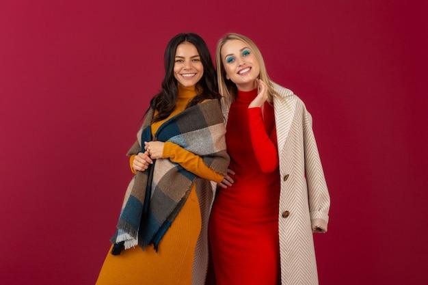 Zwei lächelnde attraktive stilvolle frauen im herbstwintermodekleid und -mantel, die lokal auf roter wand aufwerfen
