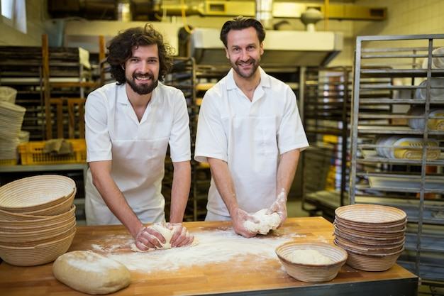 Zwei lächelnde bäcker teig kneten