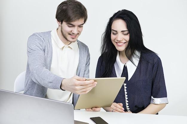 Zwei lächelnde casual designer, die mit laptop und tablet im büro arbeiten. mann frau teamarbeit.