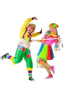 Zwei lächelnde clowns spielen ein seil isoliert über einem weißen hintergrund