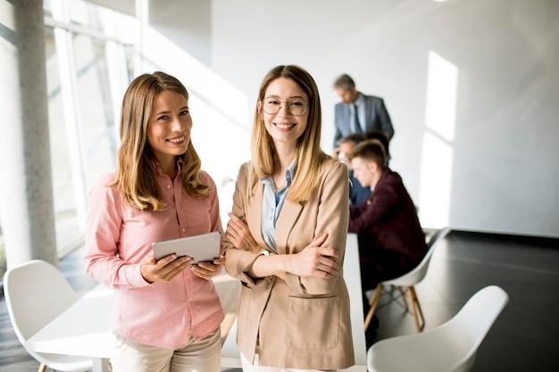 Zwei lächelnde frauen, die auf digitales tablett im büro schauen
