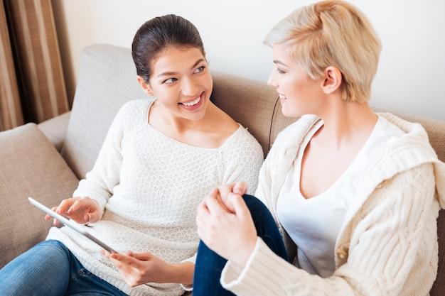 Zwei lächelnde frauen, die einen tablet-computer benutzen und sich zu hause auf dem sofa ansehen