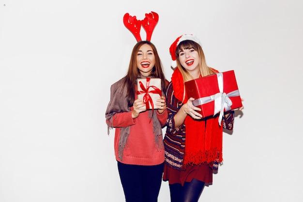 Zwei lächelnde frauen, die neujahrsgeschenke halten. trage niedliche maskeradenhüte. offenes lächeln. stimmung feiern. flash-porträt.