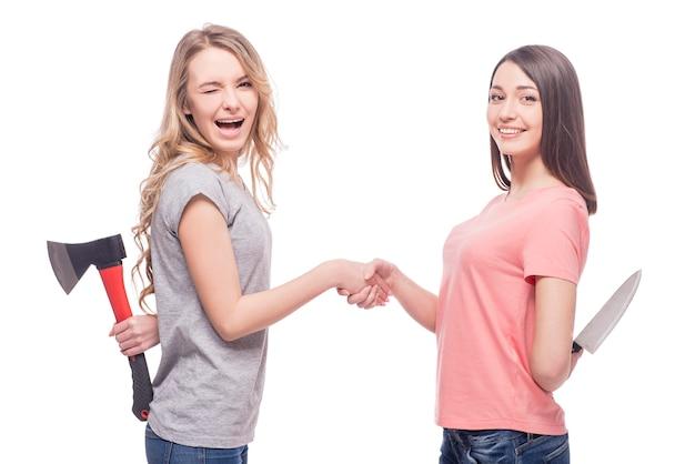 Zwei lächelnde frauen, die vertraulich stehen und messer halten.