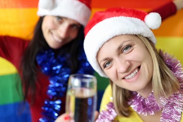 Zwei lächelnde frauen mit lgbt flagge, die neujahr und weihnachten feiern