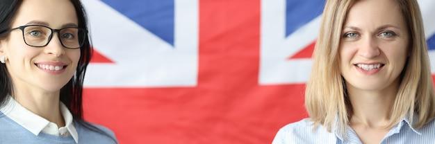 Zwei lächelnde frauen stehen mit notebooks vor britischer flagge vorbereitungssprachkurs für