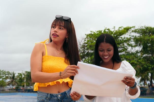 Zwei lächelnde freunde mit einer karte im freien