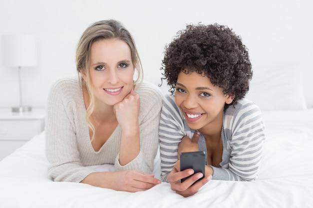 Zwei lächelnde freundinnen, die textnachricht im bett lesen