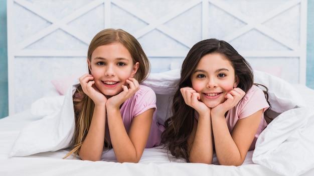 Zwei lächelnde freundinnen, die unter dem bettlaken schaut zur kamera liegen