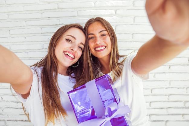 Zwei lächelnde freundinnen mit geburtstagsgeschenk