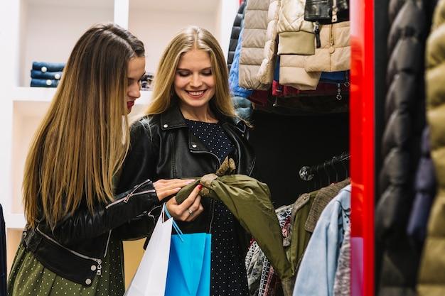 Zwei lächelnde freundinnen, welche die jacke im shop überprüfen