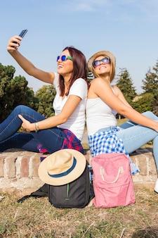 Zwei lächelnde freundinnen, welche die sonnenbrille nehmen selfie am handy tragen