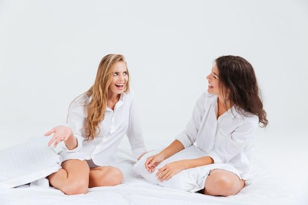 Zwei lächelnde fröhliche frauen, die hemden tragen und auf weißem bett sitzen